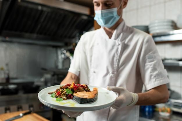 Junger profikoch in weißer uniform und schutzmaske und handschuhen mit teller mit gebratenem lachs und gemüsegarnitur in der küche