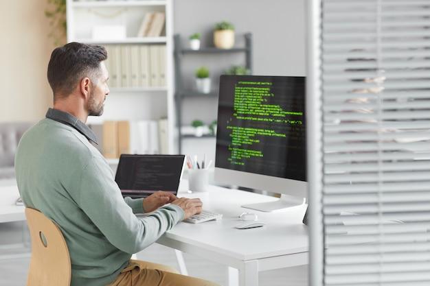 Junger programmierer, der am tisch vor dem computermonitor sitzt und neues system im büro entwickelt