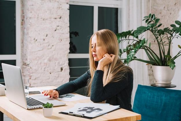 Junger psychologe, der laptop mit rorschach inkblot-testpapier auf tabelle im büro verwendet