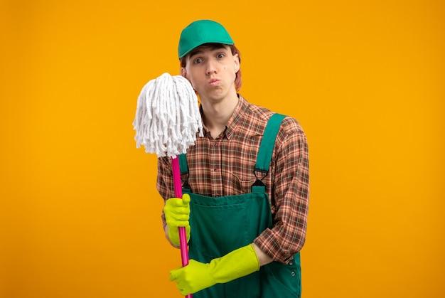 Junger putzmann in kariertem hemd-overall und mütze mit gummihandschuhen, die mopp halten und mit ernstem, selbstbewusstem ausdruck aussehen