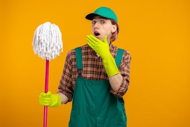 Junger putzmann in kariertem hemd-overall und mütze mit gummihandschuhen, die mopp verwirrt und überrascht über orangefarbener wand halten