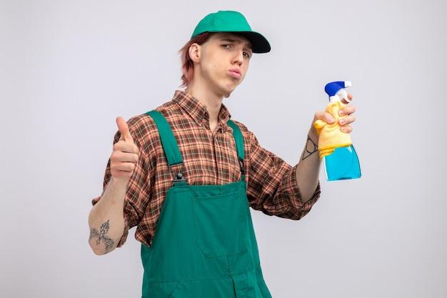 Junger putzmann in kariertem hemd-overall und mütze mit lappen und reinigungsspray nach vorne schauend mit selbstbewusstem ausdruck, der daumen nach oben über weißer wand zeigt