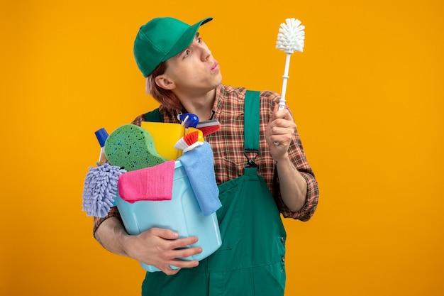 Junger putzmann in kariertem hemd-overall und mütze mit reinigungsbürste und eimer mit reinigungswerkzeugen, die die bürste fasziniert betrachten, die über der orangefarbenen wand steht