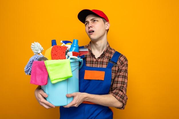 Junger putzmann in uniform und mütze mit eimer mit reinigungswerkzeugen isoliert auf orangefarbener wand