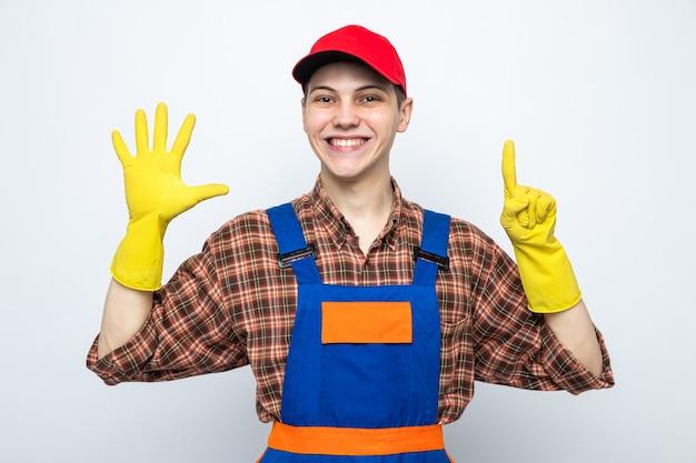 Junger putzmann in uniform und mütze mit handschuhen isoliert auf weißer wand