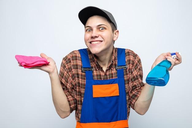 Junger putzmann in uniform und mütze mit lappen mit reinigungsmittel isoliert auf weißer wand