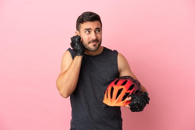 Junger radfahrer mann isoliert auf rosa hintergrund frustriert und bedeckt ohren