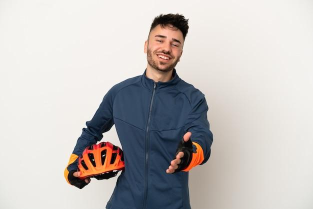 Junger radfahrer mann isoliert auf weißem hintergrund händeschütteln für ein gutes geschäft
