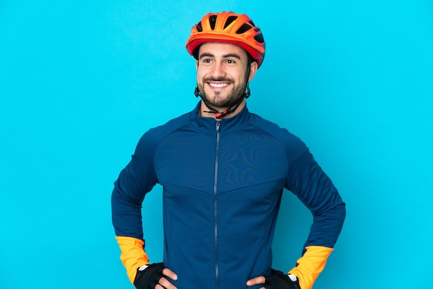 Junger radfahrermann lokalisiert auf blauer wand, die mit armen an der hüfte aufwirft und lächelt