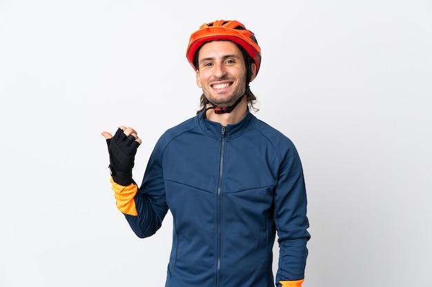 Junger radfahrermann lokalisiert auf weißer wand, die zur seite zeigt, um ein produkt zu präsentieren