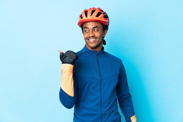 Junger radfahrermann mit zöpfen, die zur seite zeigen, um ein produkt zu präsentieren