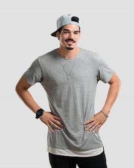 Junger rapper mann mit den händen auf den hüften, stehend, entspannt und lächelnd, sehr positiv und fröhlich