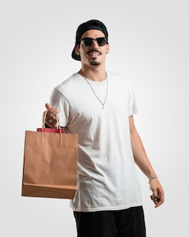 Junger rapper-mann nett und lächeln, sehr aufgeregt, einkaufstaschen tragend, bereiten vor, um zu gehen und nach neuen angeboten zu suchen