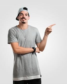 Junger rappermann, der auf die seite, lächelndes überraschendes darstellen etwas zeigt, natürlich und beiläufig