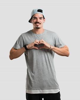 Junger rappermann, der ein herz mit den händen macht und das konzept der liebe und der freundschaft, glücklich und lächeln ausdrückt