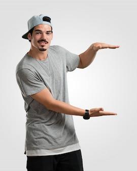 Junger rappermann, der etwas mit den händen hält, ein produkt zeigt, lächelt und nett und bietet einen eingebildeten gegenstand an