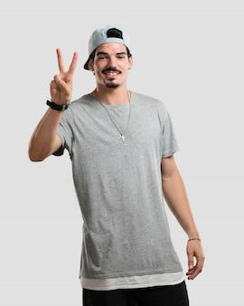 Junger rappermann, der nummer zwei, symbol der zählung, konzept der mathematik, überzeugt und nett zeigt