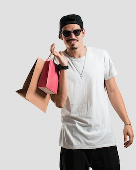 Junger rappermann nett und lächeln, sehr aufgeregt, einkaufstaschen tragend
