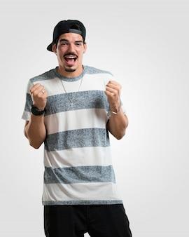 Junger rappermann sehr glücklich und aufgeregt, arme anheben, einen sieg oder einen erfolg feiern und die lotterie gewinnen