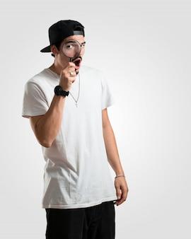 Junger rappermann überrascht und mit großen augen durch ein vergrößerungsglas schauen, etwas studierend und beweise finden