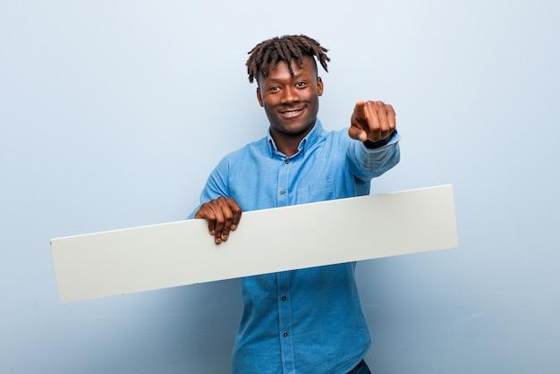 Junger rasta schwarzer mann, der ein plakat fröhliches lächeln hält, zeigt nach vorne.