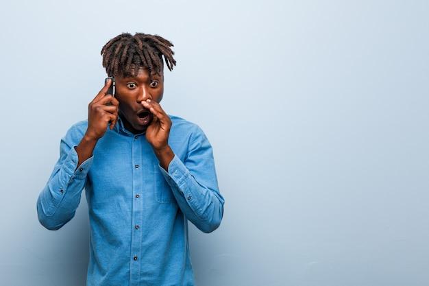 Junger rasta schwarzer mann, der ein telefonschreien aufgeregt zur front hält.