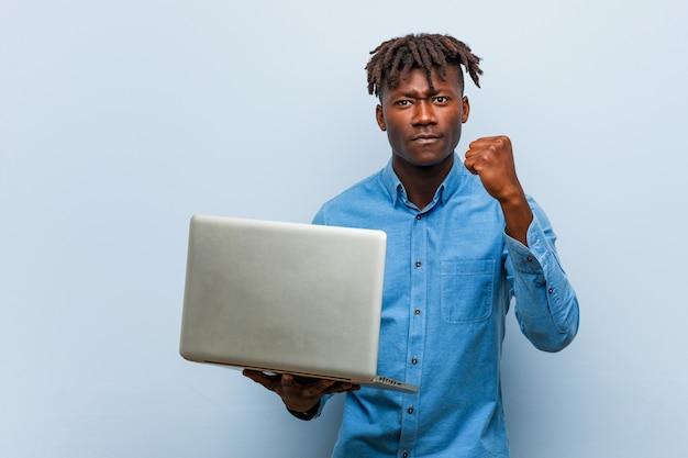 Junger rasta schwarzer mann, der einen laptop zeigt faust zur kamera, aggressiver gesichtsausdruck hält.