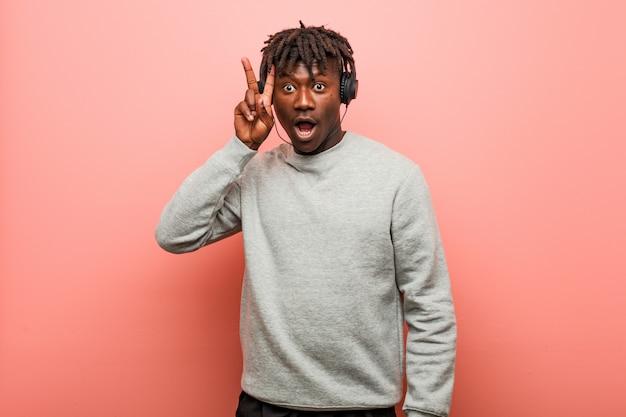 Junger rasta schwarzer mann, der musik mit den kopfhörern zeigen siegeszeichen hört und breit lächelt.