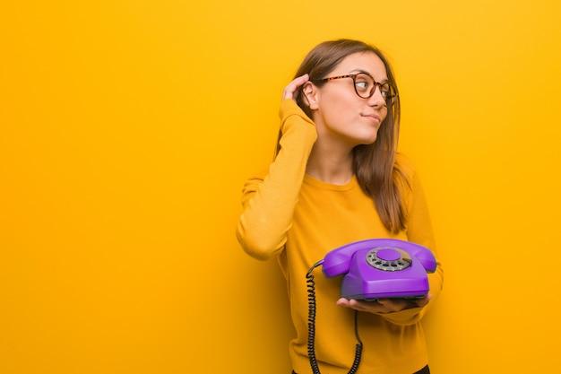 Junger recht kaukasischer frauenversuch zum hören eines klatsches. sie hält ein altes telefon in der hand.
