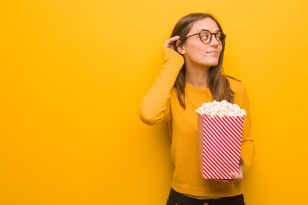 Junger recht kaukasischer frauenversuch zum hören eines klatsches. sie isst popcorn.