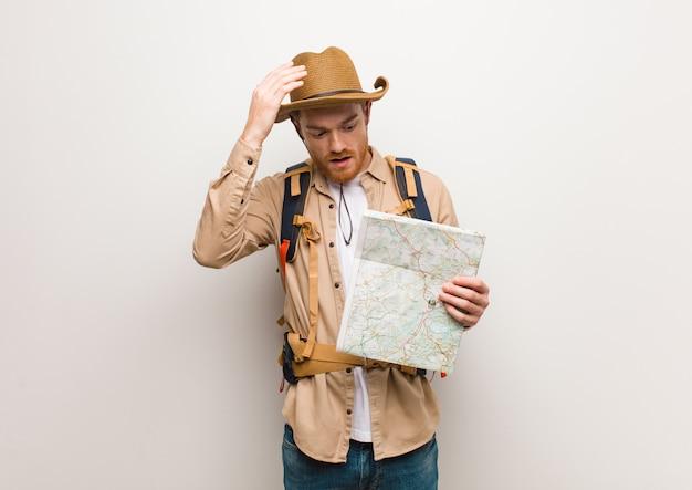 Junger redheadforschermann gesorgt und überwältigt. hält eine karte.