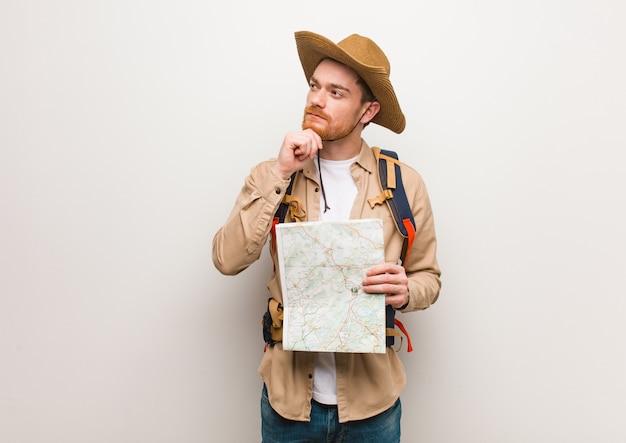 Junger redheadforschermann zweifelnd und verwirrt. hält eine karte.