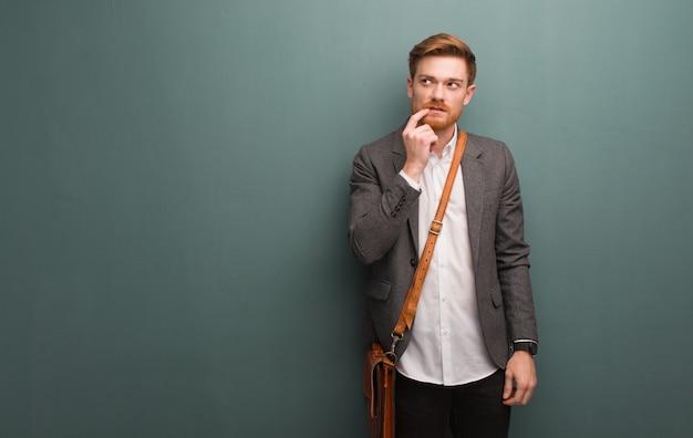 Junger redheadgeschäftsmann zweifelnd und verwirrt