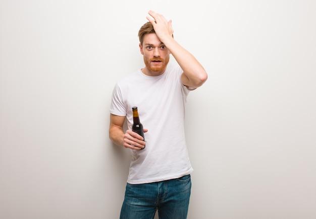 Junger redheadmann gesorgt und überwältigt. ein bier in der hand.