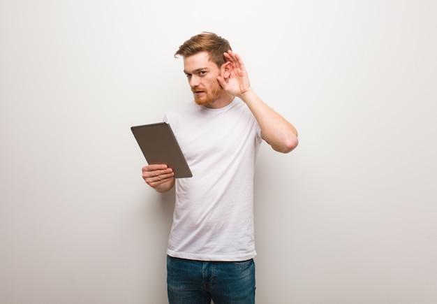 Junger redheadmannversuch zum hören eines klatsches. eine tablette in der hand.