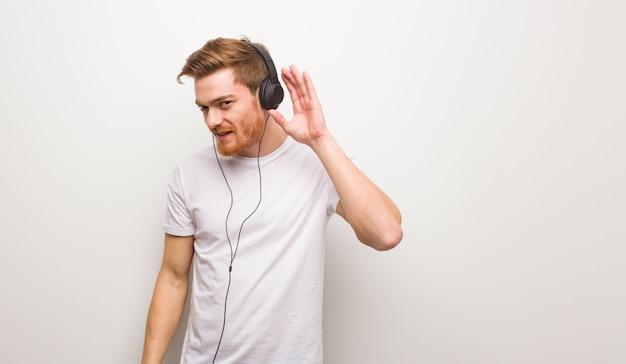 Junger redheadmannversuch zum hören eines klatsches. musik mit kopfhörern hören.