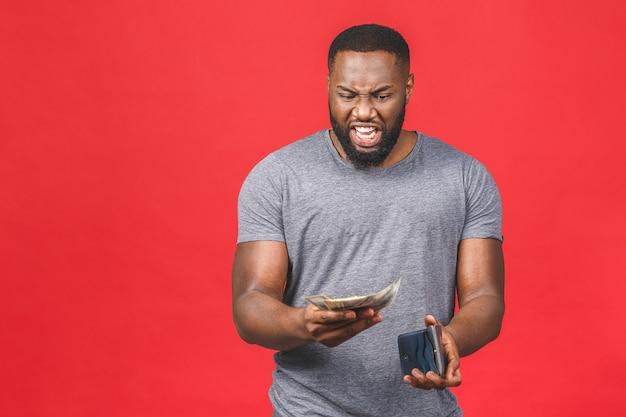 Junger reicher glücklicher afroamerikanischer mann in lässigem halten von gelddollarscheinen und brieftasche mit überraschung