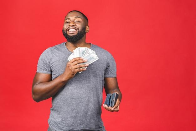 Junger reicher glücklicher afroamerikanischer mann in lässigem halten von gelddollarscheinen und geldbörse mit überraschung