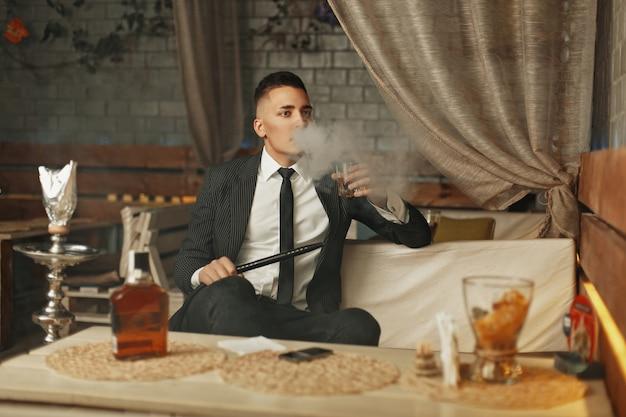 Junger reicher mann in einem eleganten anzug ruht sich in einer bar aus und raucht eine wasserpfeife