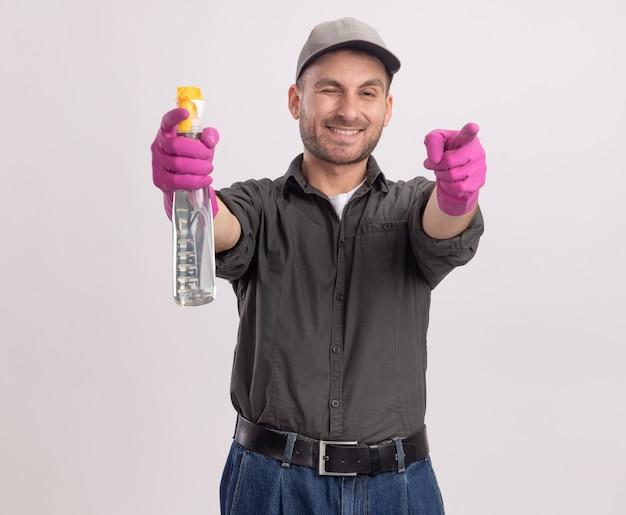Junger reinigungsmann, der freizeitkleidung und kappe in gummihandschuhen hält, die lächelnde sprühflasche hält und mit zeigefingern zeigt, die über weißer wand stehen