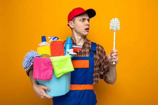 Junger reinigungsmann, der uniform und mütze trägt, die einen eimer mit reinigungswerkzeugen hält und die bürste in der hand einzeln auf orangefarbener wand betrachtet