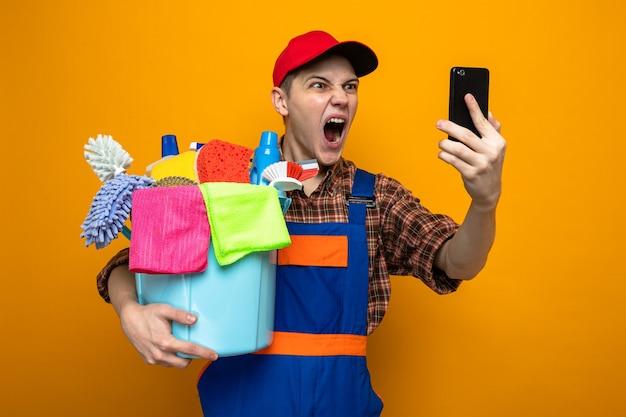 Junger reinigungsmann mit uniform und mütze, der einen eimer mit reinigungswerkzeugen hält und das telefon in seiner hand isoliert auf oranger wand betrachtet