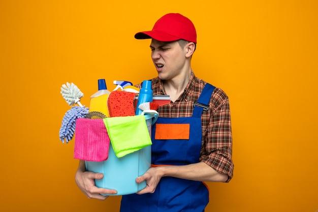 Junger reinigungsmann mit uniform und mütze, der einen eimer mit reinigungswerkzeugen isoliert auf orangefarbener wand hält und betrachtet