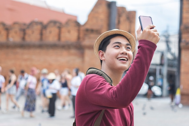Junger reisender, der ein foto mit intelligentem telefon macht.