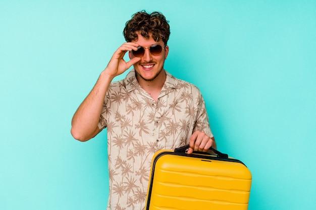 Junger reisender, der einen gelben koffer auf blauem hintergrund hält, aufgeregt, die geste auf dem auge zu halten.