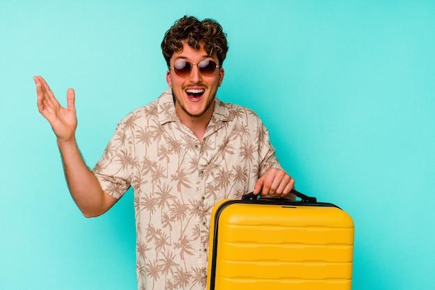 Junger reisender, der einen gelben koffer auf blauem hintergrund hält und eine angenehme überraschung empfängt, aufgeregt und die hände hebt.