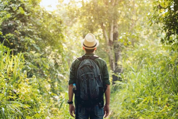 Junger reisender, der einen hut mit dem rucksackwandern im freien trägt