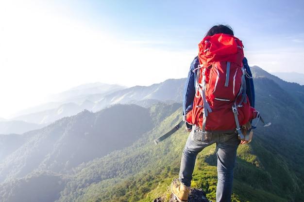 Junger reisender, der einen schauenden sonnenuntergang auf bergblick genießt