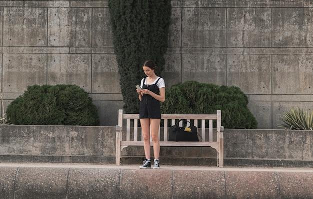 Junger reisender, der im urlaub ihr telefon überprüft