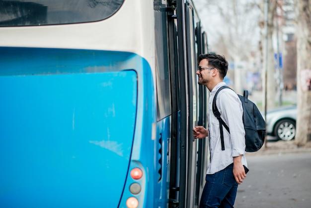 Junger reisender, der in den bus einsteigt.